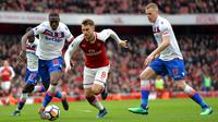Gelandang Arsenal, Aaron Ramsey, melewati kepungan pemain Stoke pada laga Premier league di Stadion Emirates, London, Minggu (1/4/2018). Arsenal menang 3-0 atas Stoke. (AFP/Oliver Greenwood)