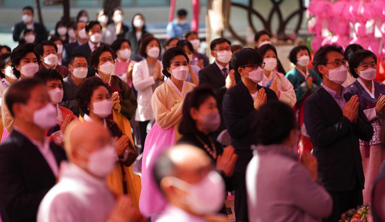 Umat Buddha memakai masker dan menjaga jarak sosial untuk mencegah penyebaran COVID-19 saat upacara merayakan ulang tahun Buddha di Kuil Jogye, Seoul, Korea Selatan, Rabu (19/5/2021). Umat Buddha mengunjungi kuil di seluruh negeri untuk merayakannya ulang tahun Sang Buddha. (AP Photo/Lee Jin-man)