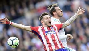 Gelandang Real Madrid, Gareth Bale, berebut bola dengan gelandang Atletico Madrid, Saul Niguez, pada laga La Liga Spanyol di Stadion Santiago Bernabeu, Madrid, Minggu (8/4/2018). Kedua klub bermain imbang 1-1. (AFP/Javier Soriano)