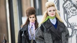 Aktris Elle Fanning membawakan busana karya Miu Miu pada pagelaran Paris Fashion Week Fall-Winter 2018, Selasa (6/3). Elle tampil berjalan menyusuri panggung tepat di depan super model Kaia Gerber. (Vianney Le Caer/Invision/AP)