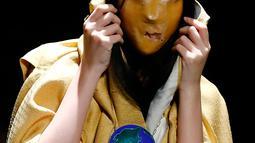 Seorang model berpose mengenakan busana dari desainer writtenafterwards selama Autumn/Winter 2016 Tokyo Fashion Week di Jepang, (16/3/2016). Writtenafterwards membawa suasana mistis pada pagelaran busana ini. (REUTERS/Thomas Peter)