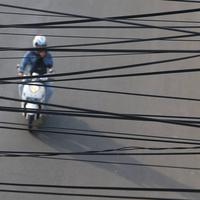 Pemotor melintas di kawasan Gunung Sahari, Jakarta, Rabu (13/7). Kurangnya penataan membuat instalasi kabel di Ibu Kota terlihat semrawut dan mengganggu pemandangan. (Liputan6.com/Immanuel Antonius)