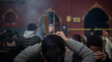 Seorang wanita berdoa untuk keberuntungan pada hari kelima Tahun Baru Imlek di Yonghegong, atau Kuil Lama di Beijing (9/2). Warga China di seluruh dunia menyambut Tahun Babi pada 5 Februari.  (AFP Photo/Nicolas Asfouri)
