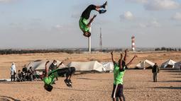 Dua pemuda melompat di udara saat menunjukkan keterampilan parkour mereka di dekat tenda warga di perbatasan Gaza, Palestina (10/4). Mereka menghibur para warga yang melakukan aksi protes di perbatasan Gaza tersebut. (AFP Photo/Said Khatib)