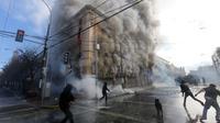 Kericuhan terjadi saat unjuk rasa di gedung Kongres di Valparaiso, Chili, Sabtu (21/5). Seorang petugas keamanan tewas saat bentrok pendemo dengan polisi. (AFP Photo/Claudio Reyes)