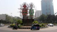 Kendaraan melintas saat Petugas PPK Kemayoran mengecat ulang Monumen Ondel-Ondel di Jalan Benyamin Sueb, Jakarta, Selasa (3/7). Pengecatan tersebut dalam rangka persiapan menyambut Asian Games pada Agustus mendatang. (Liputan6.com/Arya Manggala)