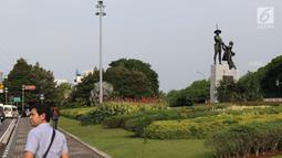 Warga melintasi di kawasan Taman Tugu Tani, Jakarta, Rabu (9/1). Lima taman yang akan direvitalisasi Pemprov DKI pada tahun ini adalah Taman Tebet, Taman Puring, Taman Tugu Tani, Taman Mataram, dan Taman Langsat. (Liputan6.com/Helmi Fithriansyah)