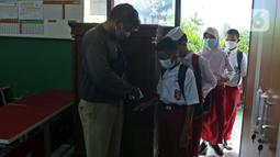 Para murid SDN Kota Baru menjalani pemeriksaan suhu tubuh saat akan mengikuti ujian penilaian akhir sekolah di SDN Kota Baru 3 Bekasi, Jawa Barat, Senin (8/6/2021). Ujian dibagi dua sesi, jam 7.00 WIB - 9.00 WIB dan 9.30 - 11.00 WIB. (Liputan6.com/Herman Zakharia)