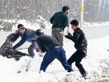 Pemuda Kashmir bermain dengan salju di tepi Danau Dal setelah salju turun di Srinagar, India bagian utara, Sabtu (5/1). Wilayah Kashmir mengalami salju selama beberapa hari yang mengakibatkan terputus jalan raya Jammu-Srinagar. (TAUSEEF MUSTAFA/AFP)