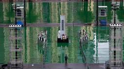 Seorang pria berjalan melewati replika Monumen Pahlawan Rakyat yang dipajang di Taman Victoria Hong Kong (4/6/2019). Puluhan ribu orang diperkirakan akan menghadiri acara nyala lilin tahunan untuk para korban tragedi Tiananmen 1989. (AP Photo/Vincent Yu)