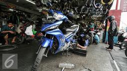 Seorang montir tengah memperbaiki mesin motor di kawasan Pasar Minggu, Jakarta, Kamis (30/6). Jelang mudik Lebaran menjadi rezeki tersendiri untuk pekerja jasa servis motor. (Liputan6.com/Yoppy Renato)