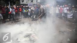 Petugas memadamkan atribut yang dibakar oleh massa saat aksi berlangsungnya unjuk rasa memperingati hari Nelayan Nasional didepan Istana Merdeka, Jakarta, Rabu (6/4). (Liputan6.com/Faizal Fanani)