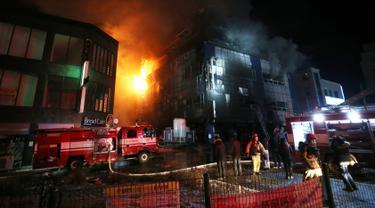 Petugas pemadam kebakaran berusaha memadamkan api yang melahap sebuah pusat kebugaran di kota Jecheon, Korea Selatan (Korsel), Kamis (21/12). Kebakaran besar itu menewaskan 29 orang dan menyebabkan puluhan lain terluka. (Kim Hyung-woo/Yonhap via AP)