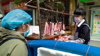 Seorang wanita membeli daging di Wuhan, ibu kota Provinsi Hubei, China tengah, (16/4/2020). Seiring meredanya epidemi COVID-19, kehidupan berangsur kembali normal di Wuhan. (Xinhua/Shen Bohan)