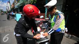 Polisi saat menilang pengendara motor pada Operasi Progo Patuh di Jl Malioboro, Yogyakarta, Rabu (18/5). Operasi Patuh di gelar secara serempak di seluruh Indonesia hingga 29 Mei 2016. (Liputan6.com/Boy Harjanto)