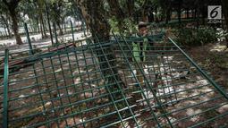 Petugas kebersihan memindahkan pagar tanaman yang dirusak pada Final Piala Presiden 2018 di Stadion Utama GBK, Jakarta, Minggu (18/2). Laga antara Persija Jakarta vs Bali United menyisakan kerusakan di dalam dan luar GBK. (Liputan6.com/Faizal Fanani)