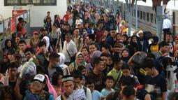Penumpang kereta api Tawang Jaya Semarang tiba di Stasiun Pasar Senen, Jakarta, Sabtu (8/6/2019). Volume penumpang arus balik melalui moda transportasi kereta api  di stasiun Stasiun Senen mengalami lonjakan pada H+3 Lebaran. (merdeka.com/Imam Buhori)