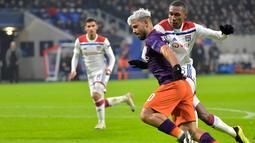 Penyerang man City, Sergio Aguero mencoba melewati pemain Lyon pada laga lanjutan liga champions yang berlangsung di stadion Parc Olympique Lyonnais, Prancis, Rabu (28/11). Manchester City imbang 1-1 kontra Lyon. (AFP/Roman Lafabregue)