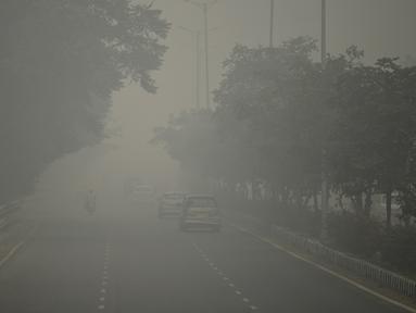 Kendaraan bermotor menembus kabut asap pekat yang menyelimuti jalan di New Delhi, Minggu (3/10/2019). Ibu Kota dari India tersebut sedang dilanda polusi udara yang sangat buruk sekaligus beracun pekan ini. (Photo by Sajjad  HUSSAIN / AFP)