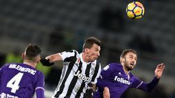 Penyerang Juventus, Mario Mandzukic (tengah) berebut bola udara dengan bek Fiorentina, German Pezzella (kanan) saat bertanding pada lanjutan Liga Serie A Italia di stadion Atemio Franchi, Florence (9/2). Juventus menang 2-0. (AFP Photo/Filippo Monteforte)