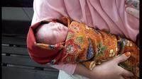 Bayi tampan saat digendong oleh istri dari salah, wrong tukang ojek yang menemukannya (Fauzan/Liputan6.com)