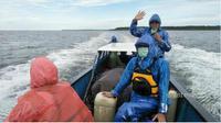 Tim Deru mengenakan jas hujan akibat cuaca yang tidak menentu saat melakukan perjalanan dengan perahu menuju Asmat. (IST/Dok Tim Deru UGM/Solopos.com)