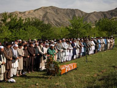 Teman dan kerabat mensalatkan jenazah kepala fotografer Agence France Presse (AFP) Afghanistan Shah Marai Faizi di Gul Dara, Kabul (30/4). (Andrew Quilty / POOL / AFP)