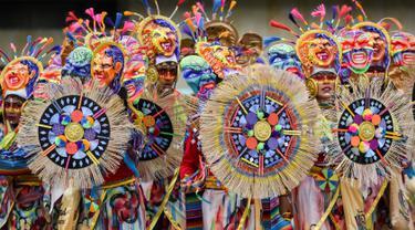 Peserta mengenakan kostum dan riasan berpose saat mengikuti parade Canto a la Tierra di Pasto, Kolombia (3/1). Parade Canto a la Tierra juga dikenal dengan karnaval orang kulit hitam dan kulit putih di Pasto. (AFP Photo/Luis Robayo)