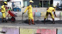 Petugas Bina Marga Pasar Minggu menambal jalan yang rusak di Jalan Raya Ragunan, Jakarta, Senin (22/4). Petugas mengaku bahwa keberadaan beton pembatas jalan justru membuat jalan di kawasan tersebut selalu rusak setiap hujan deras karena menimbulkan genangan air. (Liputan6.com/Immanuel Antonius)