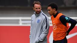 Pelatih Inggris, Gareth Southgate (kiri) berbincang dengan bek Trent Alexander-Arnold saat sesi latihan Burton-on-Trent (6/9/2019). Di grup A Inggris menempati posisi pertama dengan poin enam sedangkan Bulgaria diposisi terakhir poin dua. (AFP Photo/Paul Ellis)