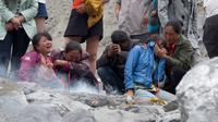 Keluarga korban menangis saat membakar dupa dan kertas ritual untuk menenangkan arwah orang yang tewas di lokasi tanah longsor di desa Xinmo, Sichuan, China (25/6). (AP Photo / Ng Han Guan)