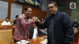 Menteri Pendidikan dan Kebudayaan Nadiem Makarim (kiri) bersalaman dengan Wakil Komisi X DPR Dede Yusuf saat rapat dengan Komisi X DPR di Kompleks Parlemen, Senayan, Jakarta, Kamis (12/12/2019). Rapat membahas penghapusan Ujian Nasional (UN) pada 2021 dan sistem zonasi. (Liputan6.com/Johan Tallo)