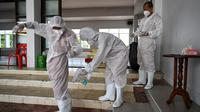 Biksu Buddha mendisinfeksi diri mereka sendiri setelah melakukan kremasi untuk korban virus corona COVID-19 di Wat Chin Wararam Worawihan, Bangkok, Thailand, 30 Juli 2021. Kasus COVID-19 di Thailand kini tengah melonjak. (Lillian SUWANRUMPHA/AFP)