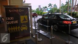 Sebuah taksi menunggu penumpang di salah satu mal di kawasan Senayan, Jakarta, Selasa (22/3). Jumlah taksi yang beroperasi sangat sedikit akibat dari aksi demo ribuan sopir taksi terkait jasa transportasi online. (Liputan6.com/Faisal R Syam)