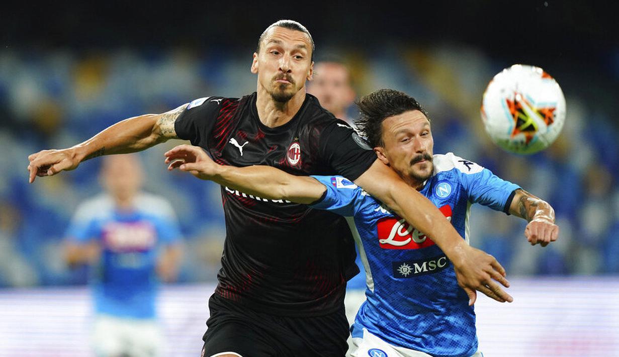 Striker AC Milan, Zlatan Ibrahimovic, berebut bola dengan  pemain Napoli, Mario Rui, pada laga Serie A di Stadion San Paolo, Minggu, (12/7/2020). Kedua tim bermain imbang 2-2. (Spada/LaPresse via AP)