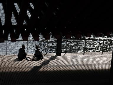Pasangan berbincang saat menikmati musim semi yang hangat di tepi air di Manhattan di New York City (8/4). Sebagian besar Pantai Timur mengharapkan suhu hangat terus sepanjang minggu. (Spencer Platt/Getty Images/AFP)