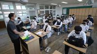 Siswa senior menghadiri kelas di Gimhae High School di Gimhae, Korea Selatan, Rabu, (20/5/2020). Siswa Korea Selatan mulai kembali ke sekolah pada hari Rabu ketika negara mereka bersiap untuk normal baru di tengah pandemi coronavirus. (Kim Dong-min / Yonhap via AP)