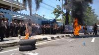Massa yang berdemonstrasi memprotes insiden Bendera Indonesia terbalik sempat membakar ban di depan Konjen Malaysia di Medan. (Liputan6.com/Reza Efendi)