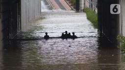 Warga melintasi banjir di terowongan Jalan Angkasa, Jakarta, Selasa (25/2/2020). Hujan yang mengguyur Jakarta sejak Senin (24/2) malam membuat sejumlah kali meluap dan menyebabkan banjir di terowongan tersebut. (Liputan6.com/Helmi Fithriansyah)