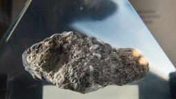 Batu dari Bulan terpajang dalam wadah kaca akrilik jelang perayaan 50 tahun misi Apollo di atas kapal USS Hornet, Alameda, California, Amerika Serikat, Selasa (16/7/2019). Tidak ada yang diizinkan untuk menyentuh batu tersebut secara langsung. (JOSH EDELSON/AFP)