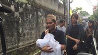 Indra Bekti menggendong sendiri anaknya menuju ke pemakaman (Rivan Yuristiawan/Bintang.com)