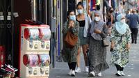 Para perempuan memakai masker di jalanan Brussel, Belgia, Rabu (12/8/2020). Penggunaan masker menjadi wajib di tempat umum di Brussel karena kasus Covid-19 naik ke tingkat kewaspadaan yang menempatkan kota itu di antara yang paling parah terkena dampak corona di Eropa. (François WALSCHAERTS/AFP)