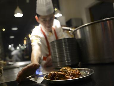 Koki menghidangkan sepiring menu kepala kelinci di sebuah restoran di Chengdu, ibu kota Provinsi Sichuan di barat daya China, 8 September 2016. Otak kelinci di negeri tirai bambu ini menjadi salah satu menu favorit warga lokal maupun asing (WANG ZHAO/AFP)