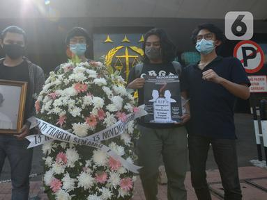 Aktivis melakukan aksi damai dengan membawa karangan bunga di Gedung Kejaksaan Agung RI, Jakarta, Jumat (13/11/2020). Mereka mendatangi Gedung Kejagung yang terbakar dengan membawa karangan bunga dan surat kepada Jaksa Agung. (merdeka.com/Imam Buhori)