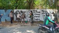 Anggota Satpol PP melakukan penghapusan mural bertuliskan kritikan di Jalan Raya Citayam, Kelurahan Depok, Kecamatan Pancoran Mas, Kota Depok. (Istimewa)