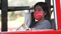 Seorang wanita mengenakan masker pelindung di sebuah bus umum di Bangkok, Thailand (14/1). Tingkat kabut asap yang sangat tinggi diperburuk oleh pola cuaca yang meningkatkan kewaspadaan di seluruh Asia. (AP Photo/Sakchai Lalit)