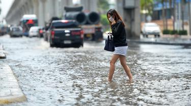 Seorang wanita menyeberangi sebuah jalan yang terendam banjir pascahujan lebat di Bangkok, Thailand (31/8/2020). (Xinhua/Rachen Sageamsak)