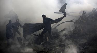 Warga memadamkan api yang membakar pasar di kamp pengungsi Nuseirat, Jalur Gaza, Palestina, Kamis (5/3/2020). Kebakaran menewaskan 11 orang dan 53 lainnya luka-luka. (MOHAMMED ABED/AFP)