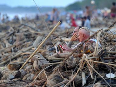 Wisatawan mancanegara duduk di dekat sampah yang terdampar akibat cuaca buruk di Pantai Kuta, Bali, Jumat (15/2). Sampah bervolume besar kembali menepi di Pantai Kuta, kali ini pesisir pantai dipenuhi sampah buah kelapa. (SONNY TUMBELAKA/AFP)