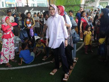 Wali Kota Tangerang Selatan Airin Rachmi Diany mencoba permainan bakiak di Taman Bermain Masyarakat (TBM) Kolong Ciputat, Tangsel, Banten, Minggu (22/7). Kegaiatan ini untuk merayakan Hari Anak Nasional. (Merdeka.com/Arie Basuki)